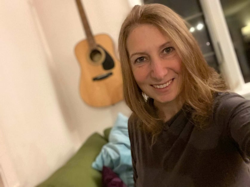 Lara Seaver is smiling, standing in front of a guitar hanging on a wall.