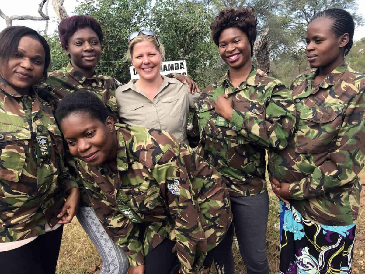 Holly Budge stands outside with members of the Black Mambas female rangers, who wear camouflage jackets.