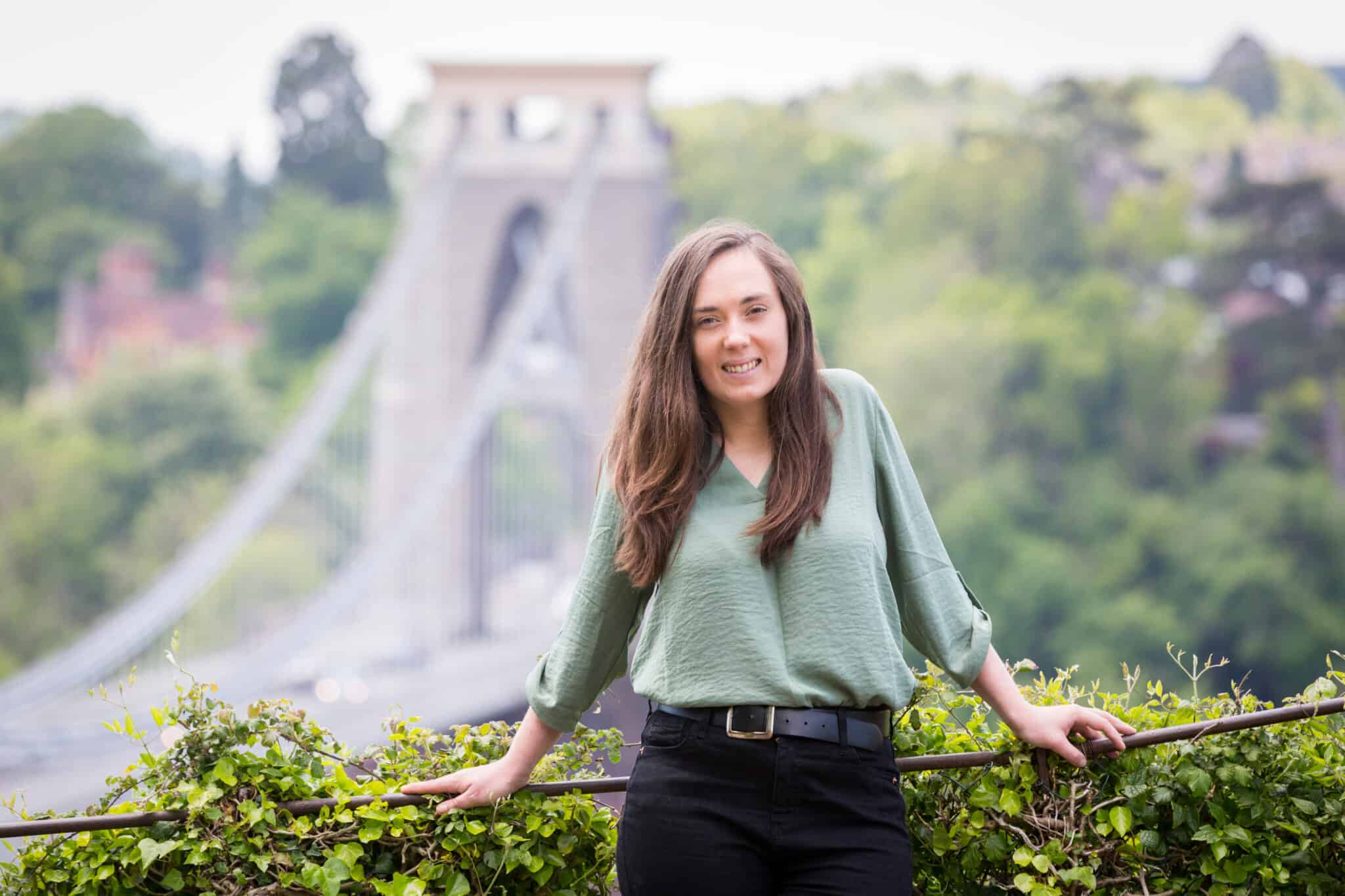 Jessie is leaning on a railing in front of Clifton Suspension Bridge. She is wearing a green blouse and black jeans.