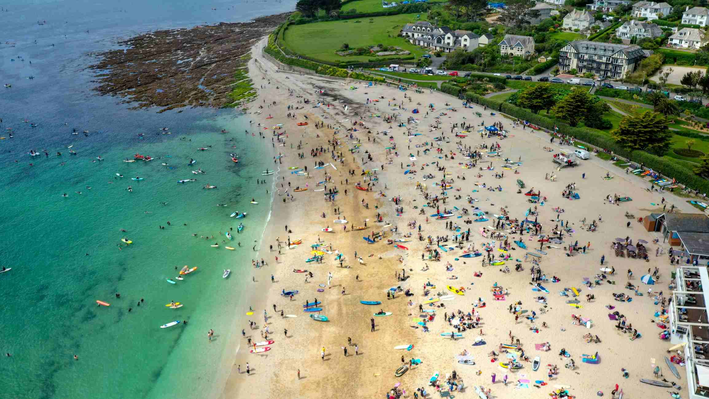 Aerial view of protesters gathered on Gyllyngvase Beach in Falmouth ahead of the paddle out. A strip of sandy beach takes up the centre of the image, with aquamarine sea to the left and green fields to the right. The beach is very busy, with many people assembled in swimsuits and wetsuits ready for the paddle out.
