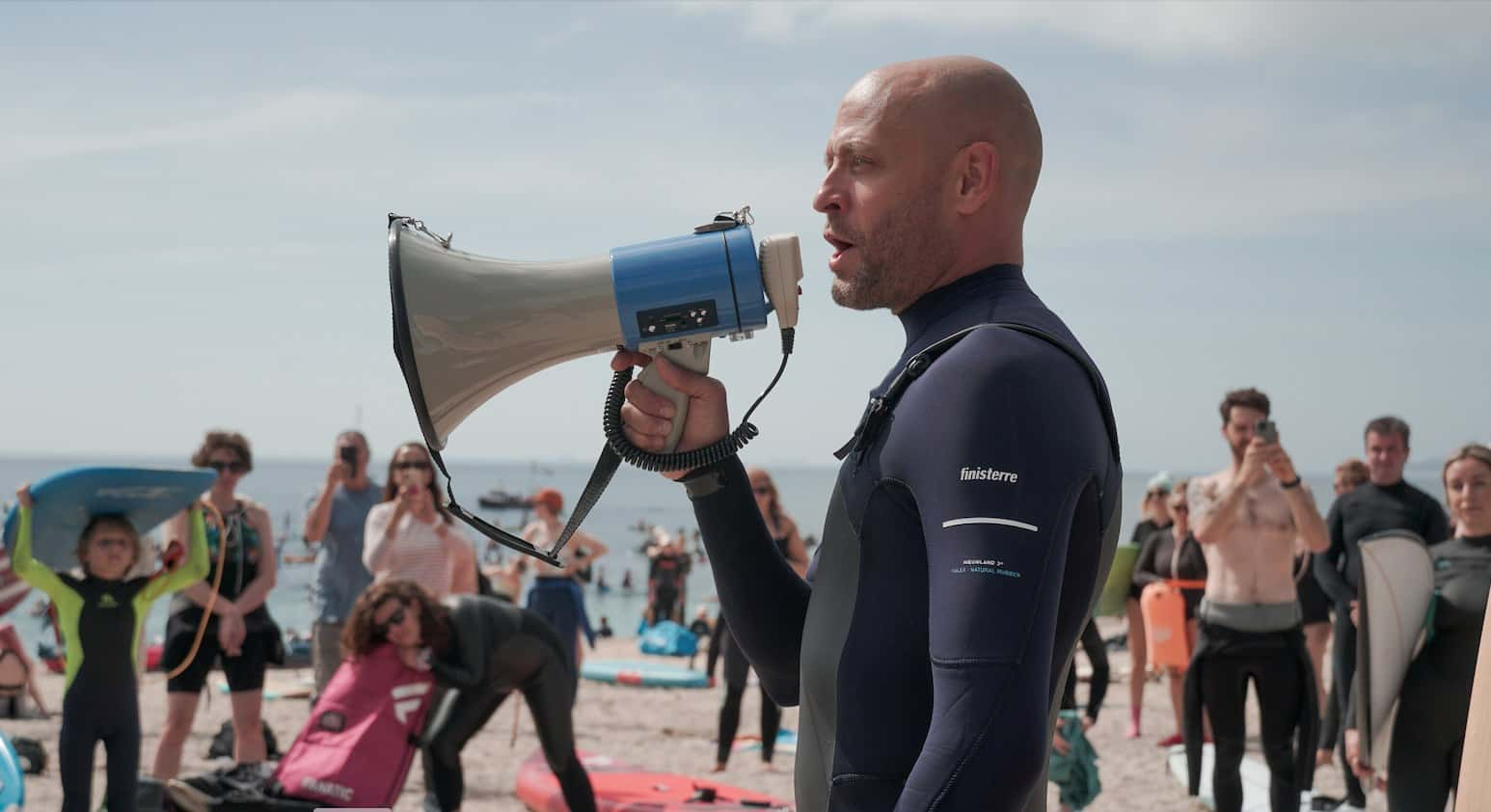 Hugo Tahholm, CEO of SAS, is pictured from the waist up in a wetsuit. He holds a megaphone and speaks through it to assembled protestors on the beach, who can be seen in the background.