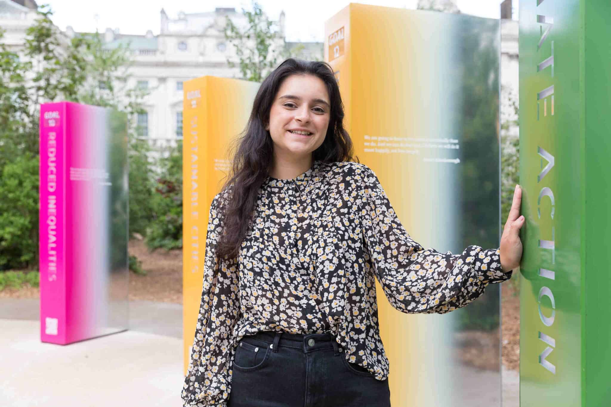 Sindhu has long black hair, and is standing in a cricle of pillars that represent the 17 sustainable development goals. She is wearing a floral print long sleeve blouse and black jeans.