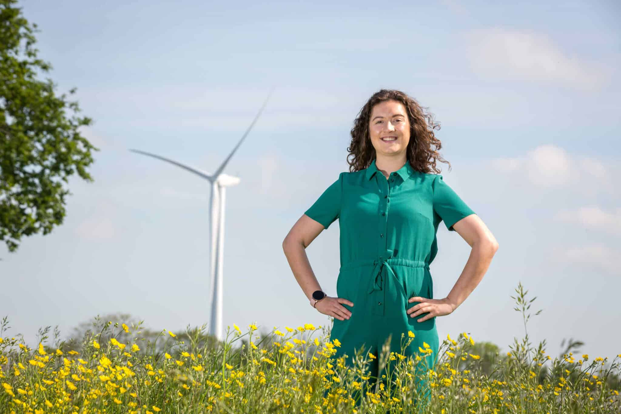Mollie is standing with her hand on her hips in a field of yellow flowers. In the background, there is a wind turbine.