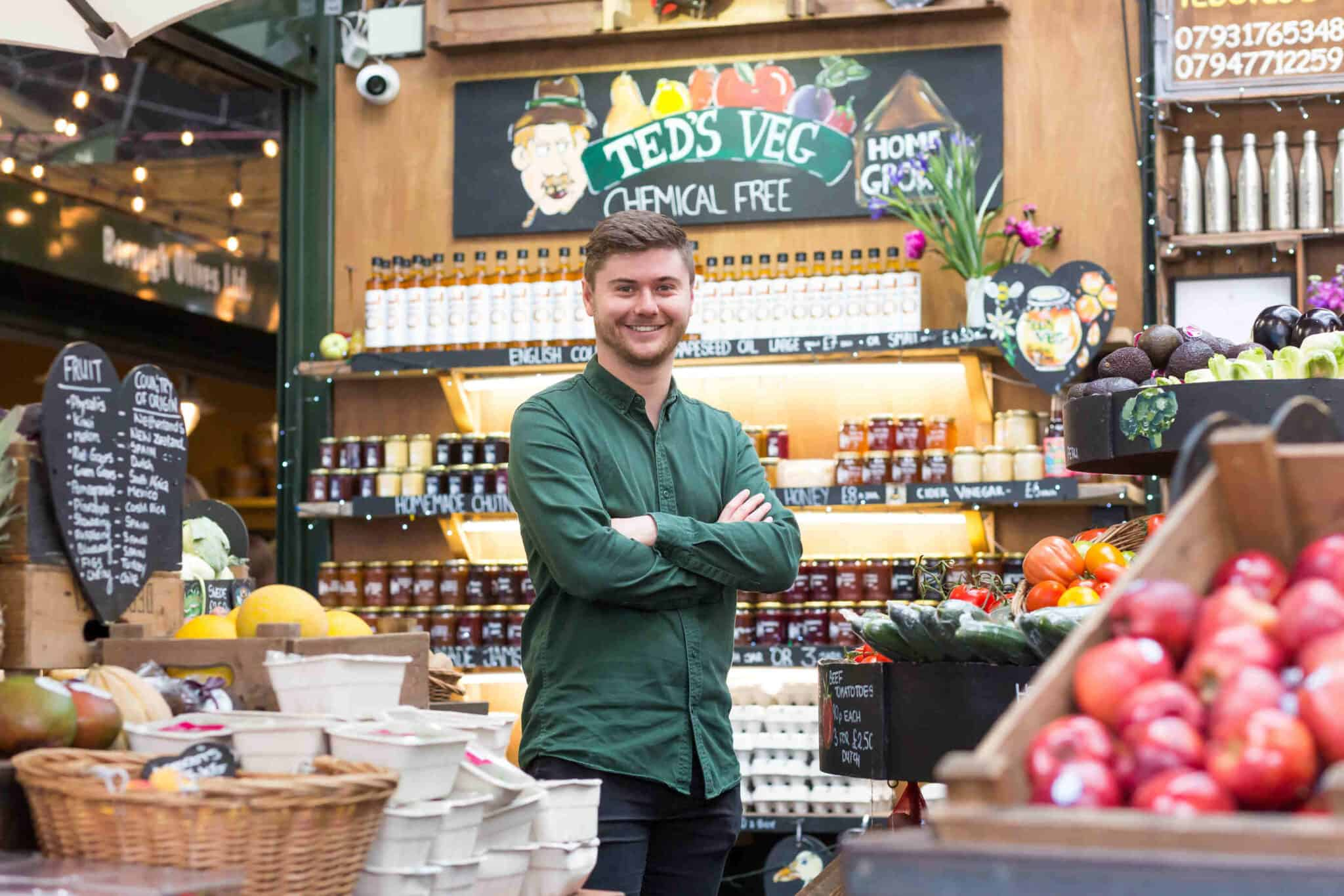 Sam is standing with his arms crossed in front of an array of fruit and vegetables. Behind him are 3 shelves laden with condiments and oils. He's wearing a green shirt and smiling.