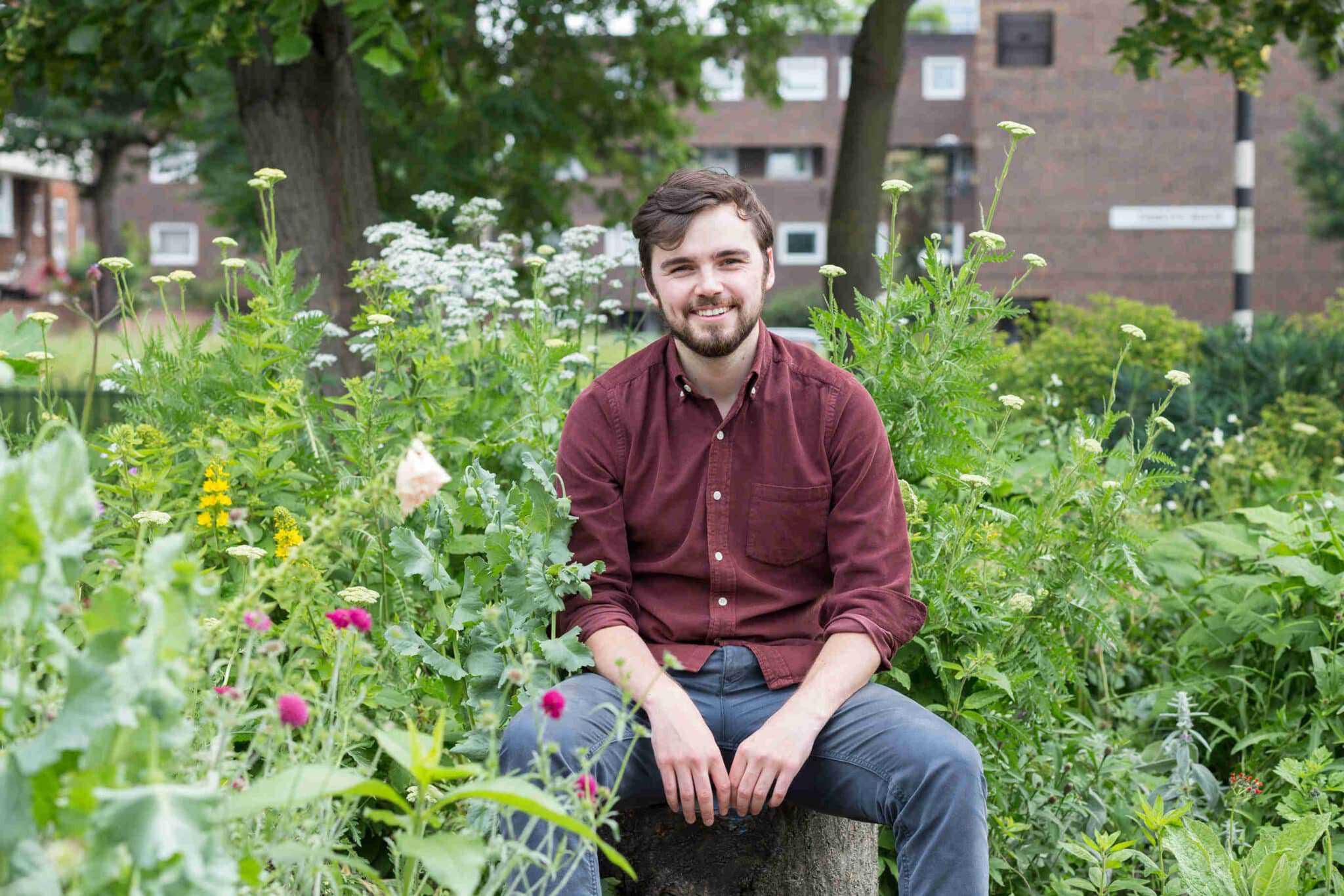 Joe is sat on a tree stump in the midst of a wildflower garden. In the distance is a block of red brick flats and a black and white sign post. Joe is wearing a red shirt and blue chinos.