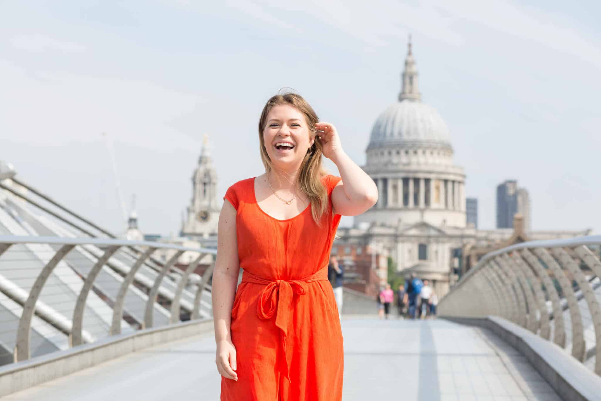 Charlie stands in front of St Pauls Cathedral and wears an orange jumpsuit. She is laughing.