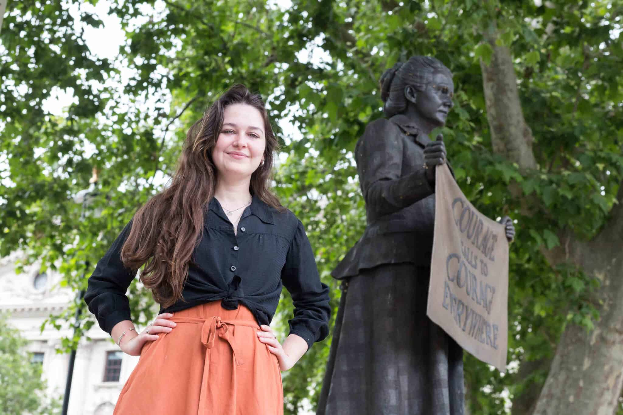 Madeleine is standing in front of Millicent Garrett Fawcett's statue in parliament Square. Her hands are on her hips.