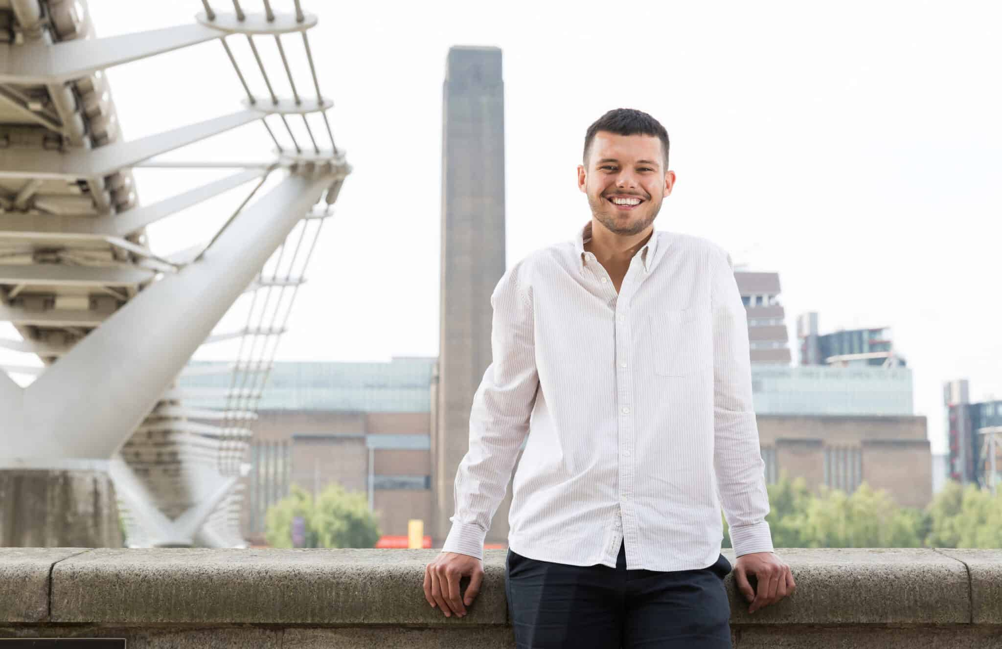 Luke is standing in front of the Tate Modern, he is leaning on a wall, smiling. he wears a white pin striped shirt and navy blue chinos.
