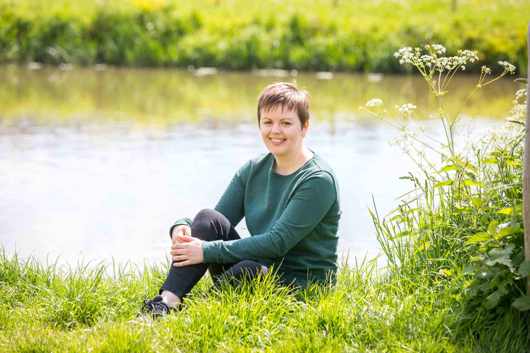 Fiona is sitting on the bright green grass in front of the River Avon. Behind her you can see the opposite riverbank. Fiona has one leg tucked into her chest which she is holding with her hands in a relaxed pose. She is smiling, wearing a green sweater, black skinny jeans and black trainers.