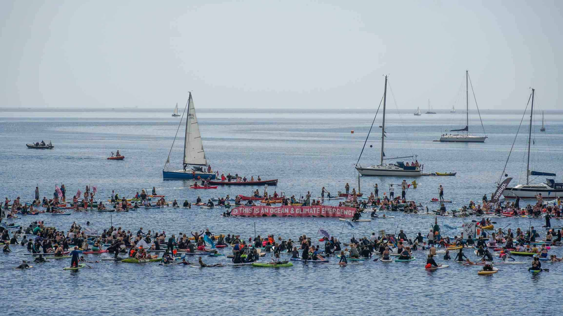 Wide-angle shot showing hundreds of people in a blue-grey sea. They have formed a ring, and in the centre of the ring protesters hold a long red banner that reads 'This is an ocean &climate emergency' alongside the SAS logo. Various yachts are dotted in the background.